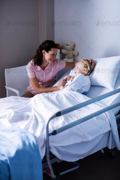 Female doctor consoling patient during visit in ward