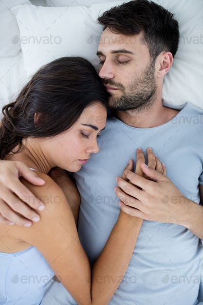 Young romantic couple sleeping on bed