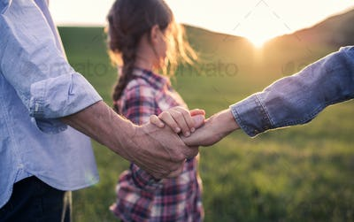 A small girl with her senior grandparents holding hands outside in nature at sunset.
