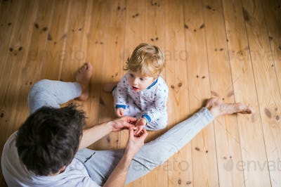 Father with a toddler boy sitting on the floor in bedroom at home. Top view.
