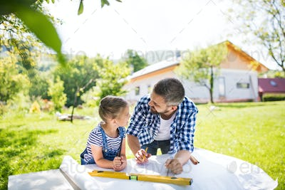 Father with a small daughter outside, planning wooden birdhouse.