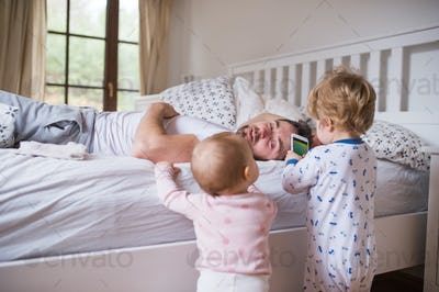 Two toddler children with smartphone and their father on bed in the bedroom.