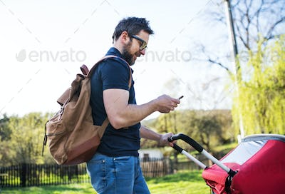 A father with smartphone and jogging stroller on a walk outside in spring nature.