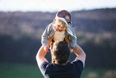 A father lifting his toddler son in the air outside in spring nature.