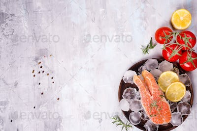 Salmon steaks on ice with lemon slice on wooden plate with tomato