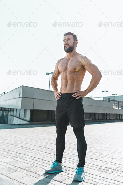 Fit fitness man posing at city