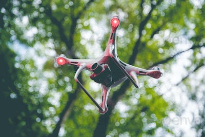 Drone with camera flying on green nature background