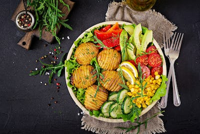 Vegetarian buddha bowl. Raw vegetables and baked potatoes in  bowl.