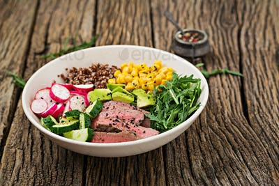 Buddha bowl lunch with grilled beef steak and quinoa, corn, avocado, cucumber