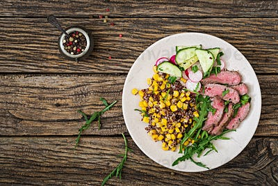 Bowl lunch with grilled beef steak and quinoa, corn, cucumber, radish and arugula