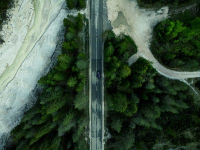 Car driving on alpine road in forest, top down aerial drone view