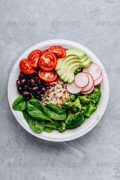 Burrito Buddha Bowl with wild rice and broccoli, spinach, black beans, tomatoes, avocado and radish