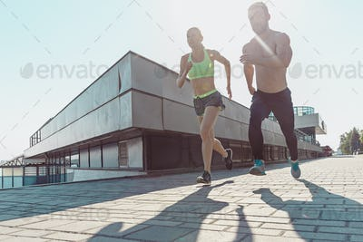 Pretty sporty woman and man jogging at city