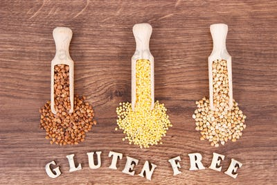 Gluten free inscription with various groats on rustic board, healthy food concept