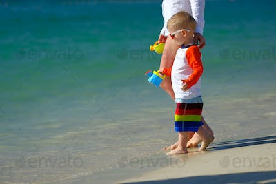 Two year old toddler walking on beach with mother
