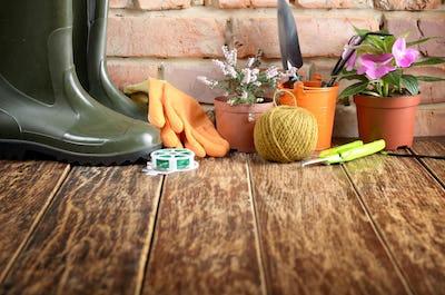 Gardening tools of shovel rake rope gloves on wooden floor
