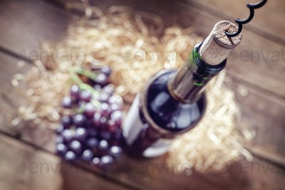 Bottle of wine, cork and corkscrew on wooden table