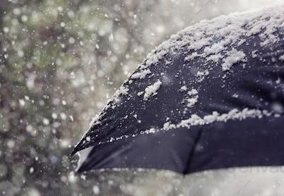 Snow flakes falling on umbrella