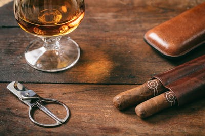 Cuban cigars closeup on wooden desk, blur glass of brandy