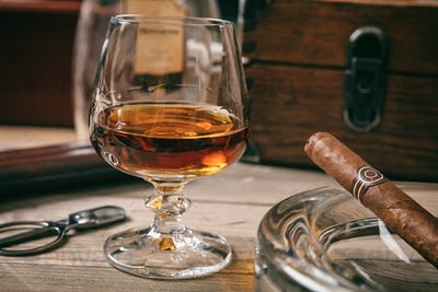 Cuban cigar and a glass of brandy on wooden background, closeup view with details