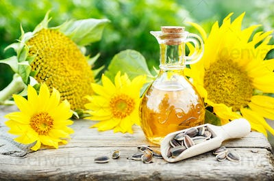 Sunflower Oil with seeds on old wooden table.