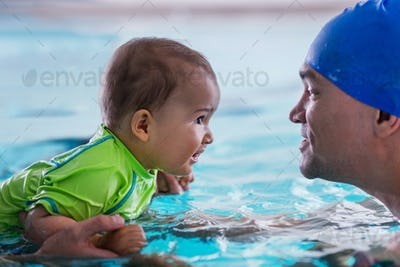 Father with baby boy in the swimming pool on swimming class