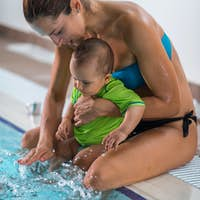 Mother with baby boy in the swimming pool on swimming class