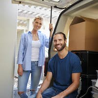 Portrait Of Couple Sitting In Back Of Removal Truck On Moving Day