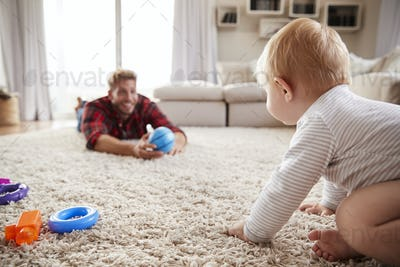 Young father playing with toddler son on the floor at  home