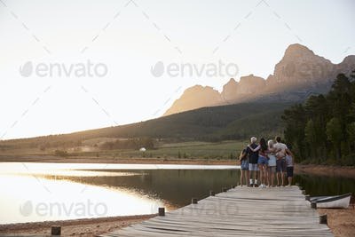 Rear View Of Multi Generation Family Standing On Jetty By Lake