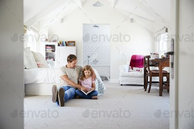 Father and daughter reading a book together in her bedroom