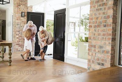 Visiting grandparents hugging grandchildren as they arrive
