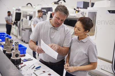 Engineer And Female Apprentice Discussing Job Sheet In Factory