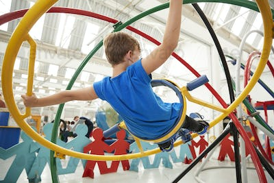 Young white boy using a human gyroscope, back view