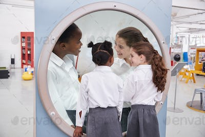 Schoolgirls looking in a magnifying mirror at science centre