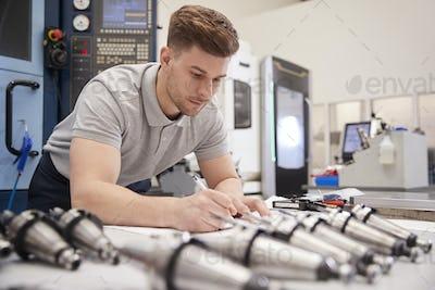 Male Engineer Measuring CAD Drawings In Factory