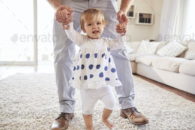 Father helping daughter learn to walk in the sitting room
