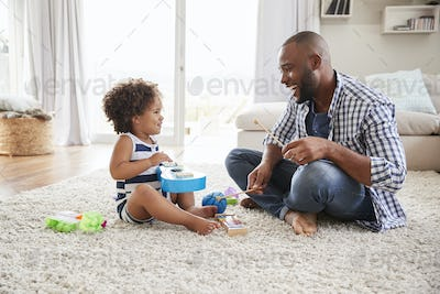 Dad and toddler daughter playing instruments in sitting room
