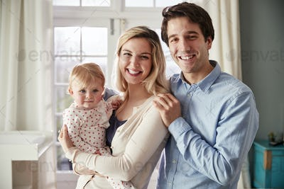 Portrait Of Smiling Family Holding Baby Daughter In Nursery