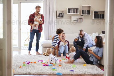 Adult friends with toddlers socialising in sitting room