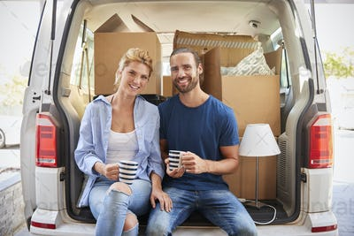 Couple Taking A Break In Back Of Removal Truck On Moving Day