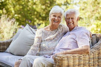 Happy senior couple sitting in garden looking to camera