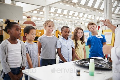 Lab technician showing graduated cylinder to a group of kids