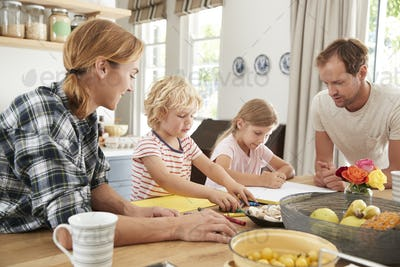 Young white family busy together in their kitchen, close up