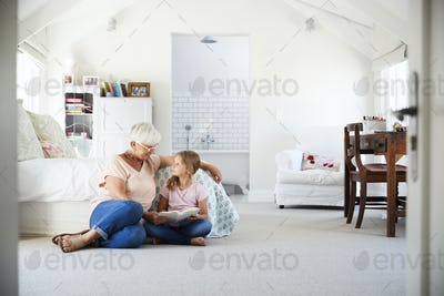 Grandmother and granddaughter reading a book in her bedroom