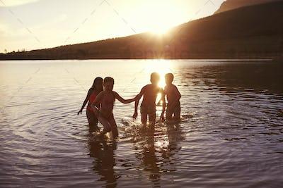 Children With Friends Enjoying Evening Swim In Countryside Lake