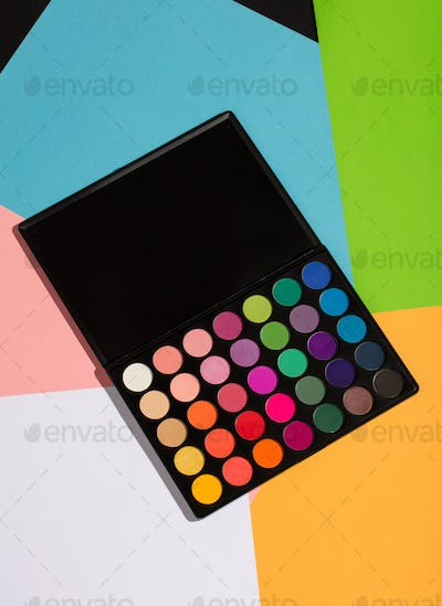 Eyeshadow palette laying on a colorful background.
