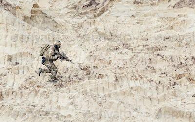 Soldier with carbine running alone through desert