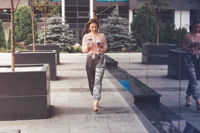 Smiling businesswoman with coffee cup walking on the street and making a phone call