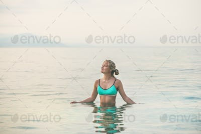 Young woman in blue swimsuit standing in still sea waters